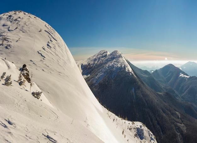 美しい冬の風景。白い深い雪、地平線に伸びる遠くの木質山脈のパノラマ、青い空のコピースペースの背景に明るく輝く太陽光線のある急な山の丘の斜面。