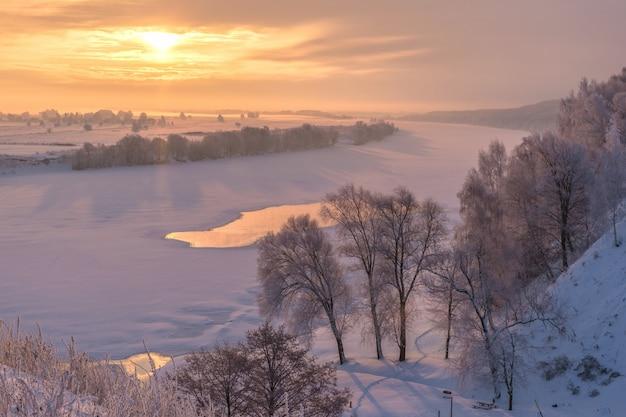 Красивый зимний пейзаж. восход солнца над рекой. заснеженные деревья на берегу реки.