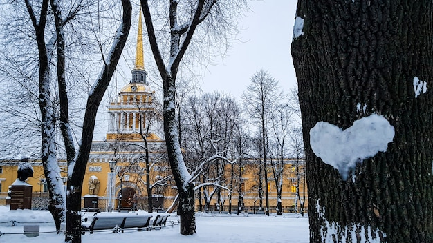 Beautiful winter landscape with heart of snow on tree trunk and spire of admiralty building, saint petersburg, russia
