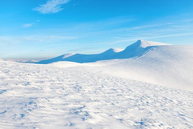 青い空の下で雪の山々と美しい冬の風景