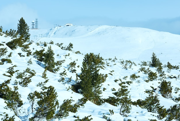 Beautiful winter mountain landscape with ski lift and ski run on slope