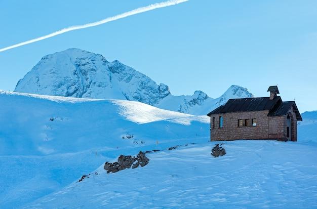 언덕 꼭대기에 예배당이있는 pordoi pass (이탈리아 dolomites)에서 아름다운 겨울 산 전망.