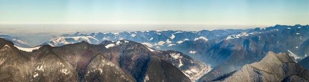 신선한 눈으로 아름 다운 겨울 파노라마입니다. 가문비나무 소나무가 있는 풍경, 태양광이 있는 푸른 하늘, 배경에 높은 카르파티아 산맥.