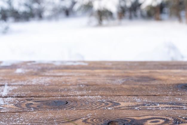 아름 다운 겨울 장면입니다. 눈 덮인 크리스마스 자연 배경의 흐릿한 배경, 빛나는 보케에 있는 나무 탁자. 제품 전시를 위해 크리스마스 시간 모형