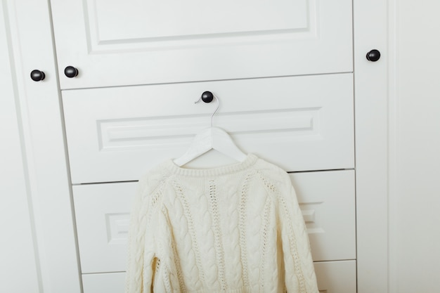 Beautiful winter sweater for girls on hanger at the background of white wardrobe