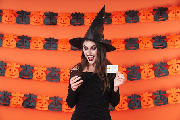 Beautiful witch girl in black halloween costume holding smartphone and credit card isolated over orange pumpkin wall