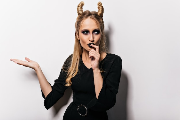 カーニバルでポーズをとるドレスの美しい魔女。ハロウィーンを祝う吸血鬼の衣装で物思いにふけるブロンドの女性。