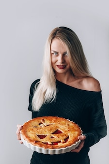 Beautiful witch with a pie for halloween