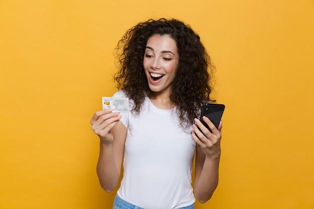 Красивая женщина 20-х годов в повседневной одежде держит мобильный телефон и кредитную карту, изолированную на желтом
