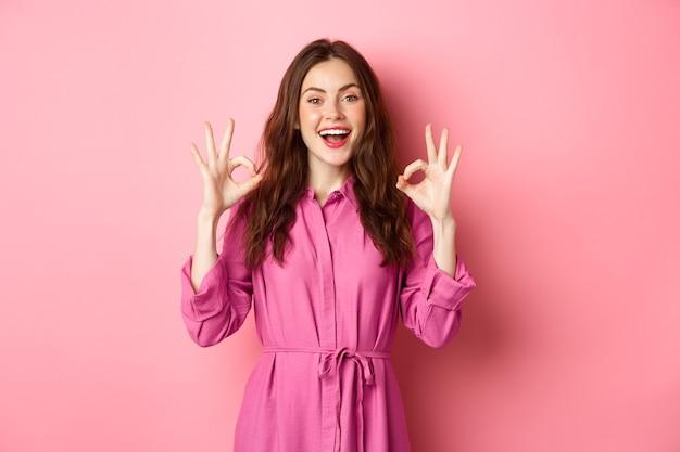아름다운 여성 20 대, 승인, 고개를 끄덕이고 미소를 지으며 만족스럽고 서서 분홍색 벽 위에 서 있습니다.