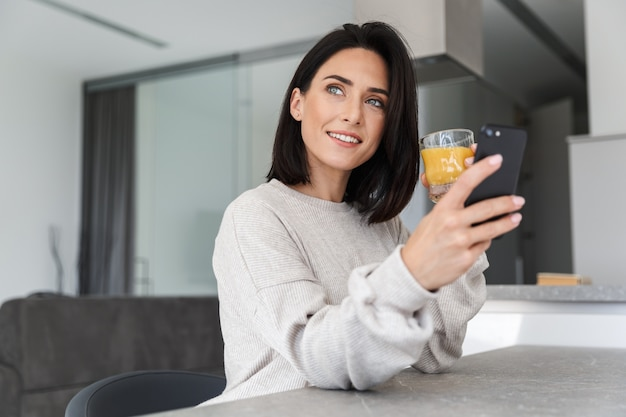 Beautiful woman 30s drinking orange juice and using mobile phone, while resting in bright modern room