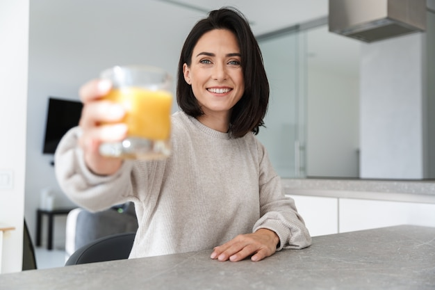 Beautiful woman 30s drinking orange juice, while resting in bright modern room