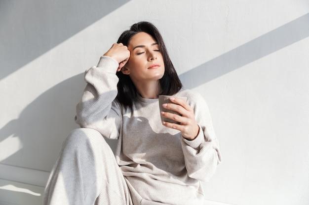 Красивая женщина 30 лет держит чашку с чаем, сидя на белой стене в помещении