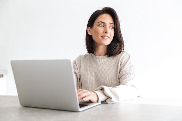 Красивая женщина 30 лет работает на ноутбуке, сидя на белой стене в светлой комнате