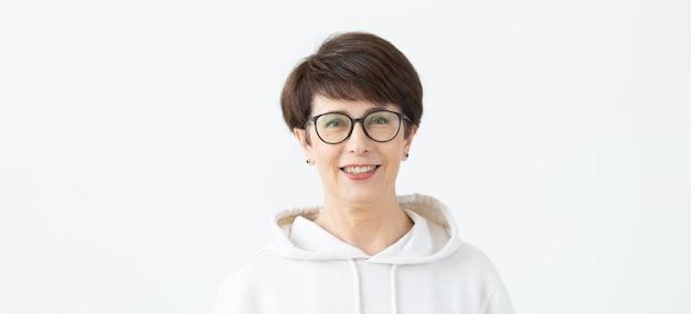 コピースペースと白い背景の上に立っているメガネで40〜50歳の美しい女性