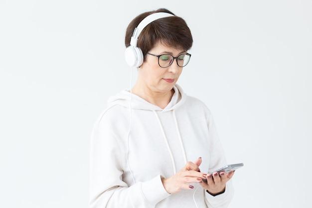 大きなヘッドフォンで音楽を聴き、白でタブレットを保持している40〜50歳の美しい女性