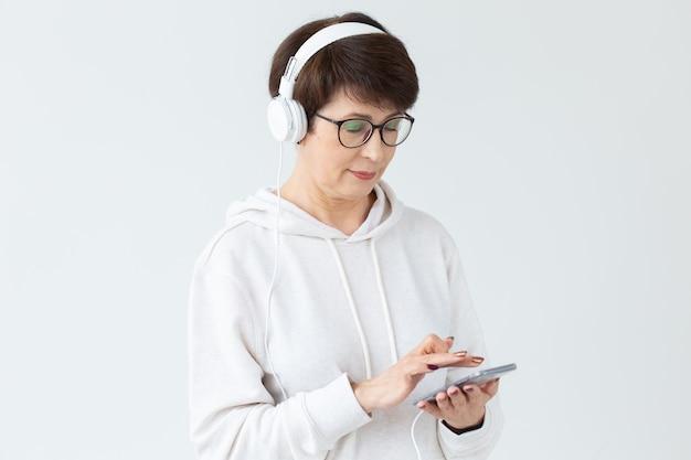 白い表面にタブレットを保持している大きなヘッドフォンで音楽を聴いている40〜50歳の美しい女性