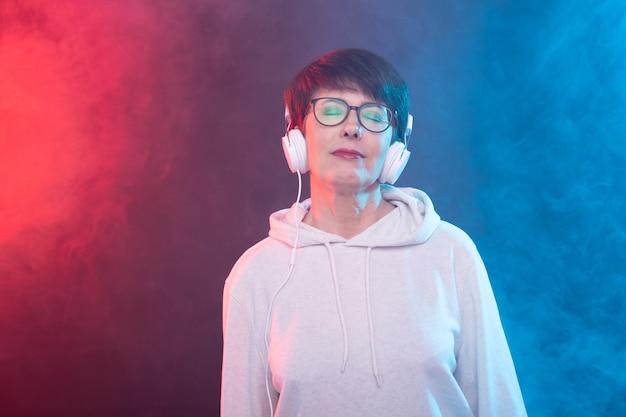 青い壁に大きなヘッドフォンで音楽を聴いている40〜50歳の美しい女性。
