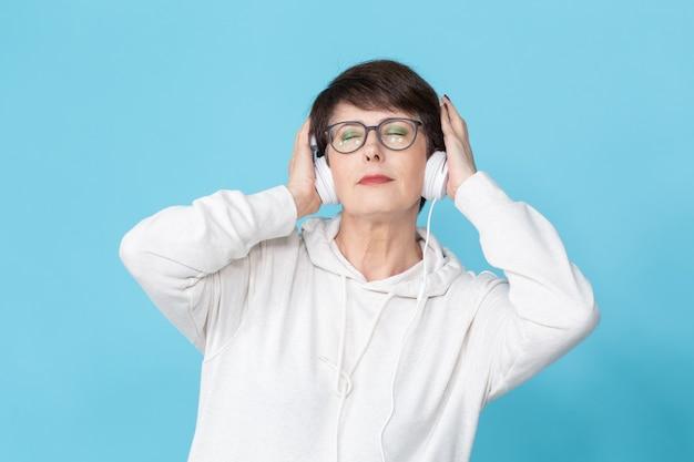 青い壁に大きなヘッドフォンで音楽を聴いている40-50歳の美しい女性。