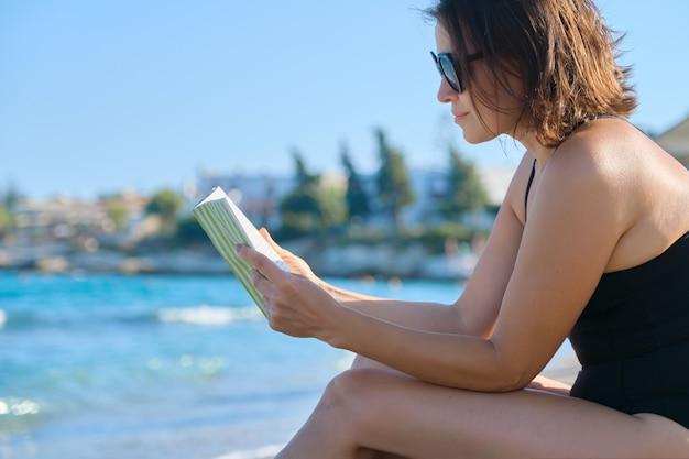 Красивая женщина 40 лет отдыхает на песчаном пляже, женщина читает книгу, наслаждаясь морем и закатом