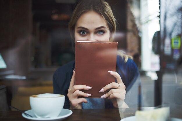 美しい女性カフェスナック朝食で一杯のコーヒー