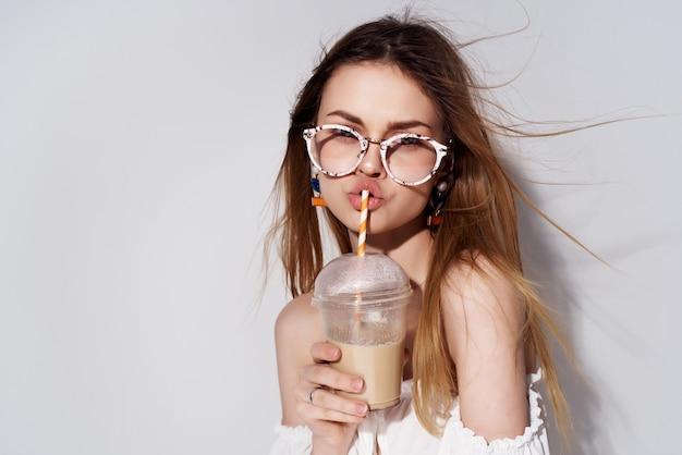 아름 다운 여자 손에 음료와 함께 유리 패션 밝은 배경. 고품질 사진