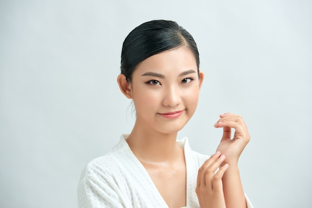 シャワーの後の美しい女性。白い背景の上の完璧なメイクでアジアの女性の写真。美容とスキンケアのコンセプト
