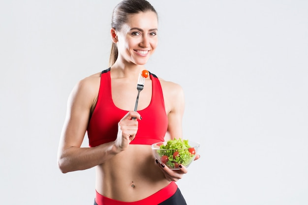 Beautiful woman after workout with a salad isolated