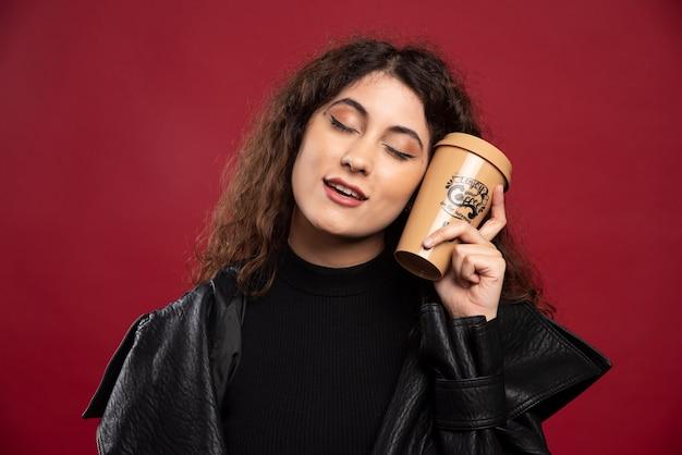 Bella donna in abito tutto nero che tiene una tazza.
