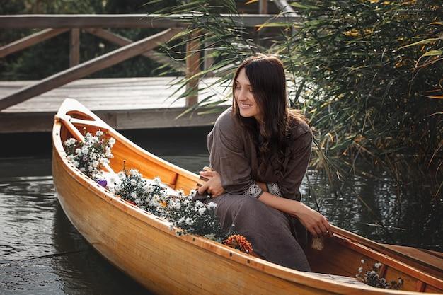 自然と湖のプライバシーに浮かぶ木製のボートに一人で美しい女性