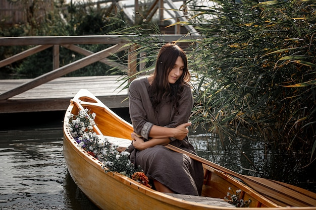Beautiful woman alone in a wooden boat floating on the lake privacy with nature