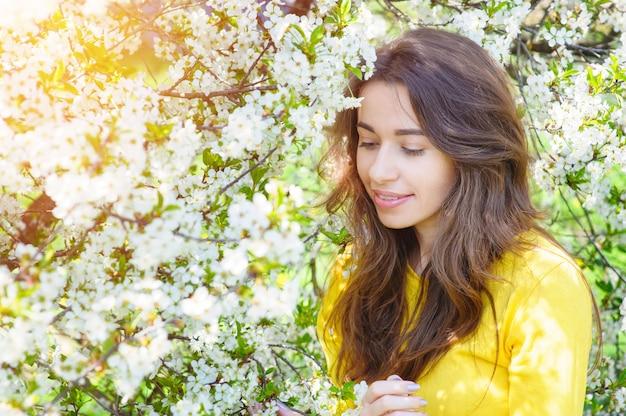 Beautiful woman among blossom trees