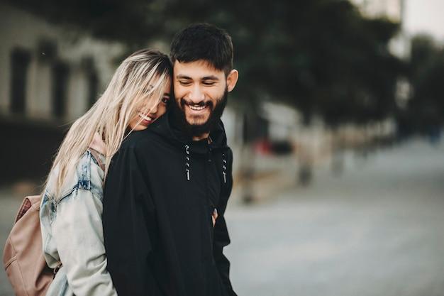 Красивая женщина и бородатый красавец, стоя в объятиях на улице