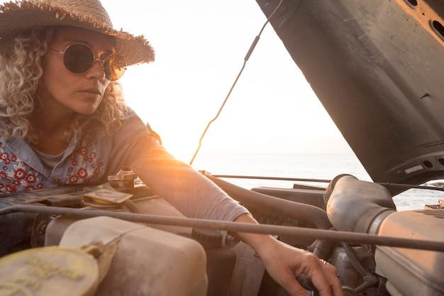 美しい女性と女性が屋外で車のエンジンをチェックするエンパワーメントライフスタイルのコンセプト-旅行と旅行中に一人で車を修理する独立したライフスタイルの女性