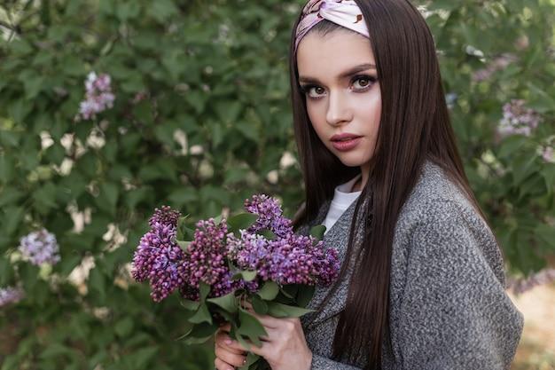 아름 다운 여자와 꽃 나무입니다. 놀라운 보라색 꽃이 있는 세련된 회색 코트를 입은 귀여운 사랑스러운 소녀 모델은 공원에서 자연을 즐깁니다. 야외에서 라일락의 꽃다발과 함께 매력적인 아가씨입니다. 봄 시간입니다.