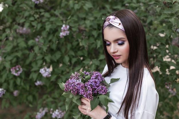 아름 다운 여자와 꽃 나무입니다. 놀라운 보라색 꽃이 있는 세련된 흰색 옷을 입은 귀여운 사랑스러운 소녀 모델은 공원에서 자연을 즐깁니다. 야외에서 라일락의 꽃다발과 함께 매력적인 아가씨입니다. 봄.