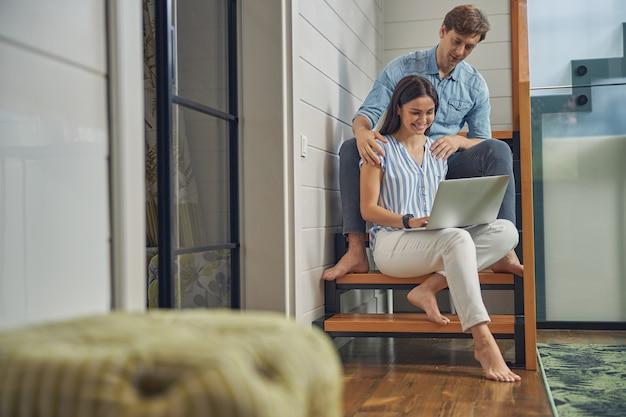 현대 집의 계단에 앉아있는 동안 노트북에서 시간을 보내는 아름 다운 여자와 잘 생긴 남자