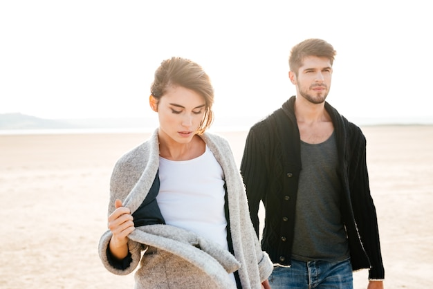 秋の海辺を歩く美女とハンサムな男