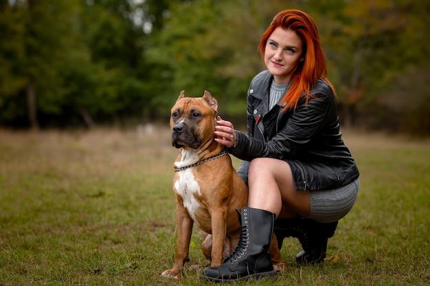 美しい女性と秋の公園で彼女のアメリカンスタッフォードシャーテリア犬 Premium写真