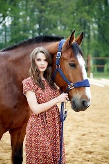 美しい女性と屋外の馬。