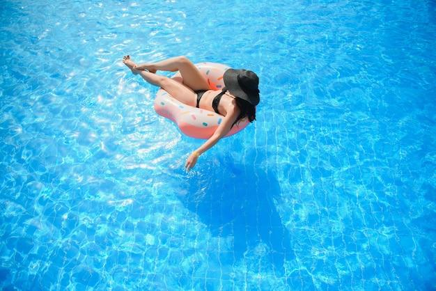 수영장에서 도넛 모양의 아름다운 여자와 풍선 수영 반지
