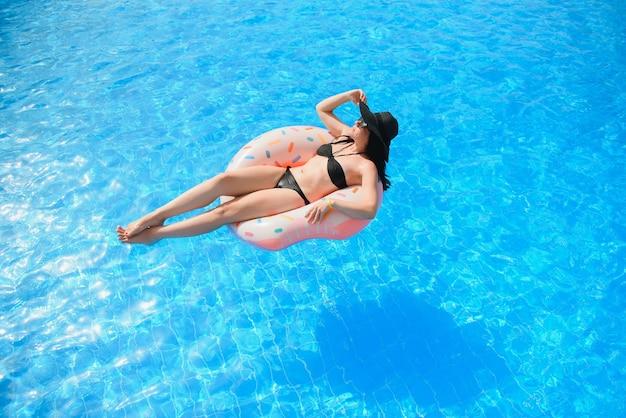 Красивая женщина и надувное кольцо для плавания в форме пончика в бассейне