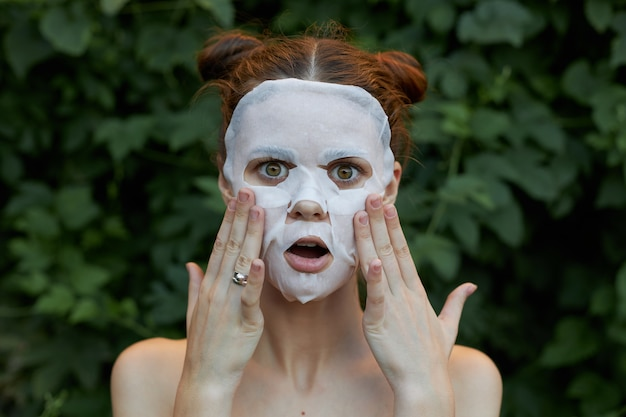 美しい女性のアンチエイジングマスクあなたの手であなたの顔に触れることに驚いた