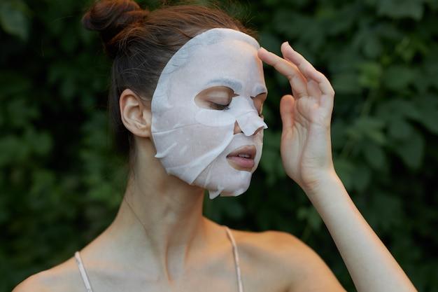 아름다운 여자 주름 방지 마스크. 감은 눈과 투명한 종이 피부 관리. 백그라운드에서 녹색 잎