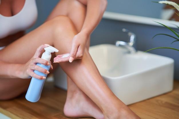 화장실에서 다리에 밤을 적용하는 아름 다운 여자