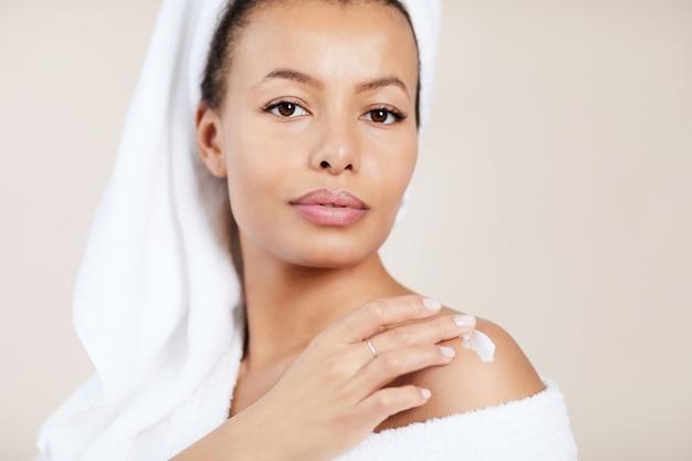 Красивая женщина, применяя крем для тела