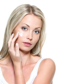 Bella donna che applica crema cosmetica sul viso - isolato