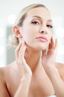 化粧水を適用する美しい女性