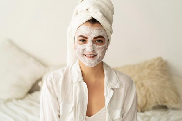 顔のマスクを適用する美しい女性。化粧品。