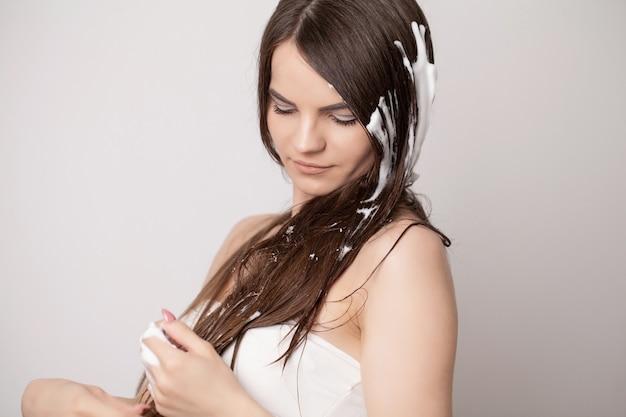 Красивая женщина, применяя кондиционер для волос в ванной комнате.